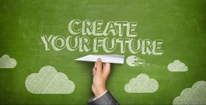 Create your future concept on green blackboard with businessman hand holding paper plane
