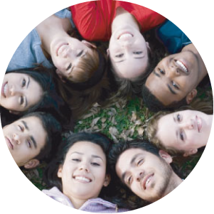 Group lying on the ground, in a circle, heads in the centre looking up at camera