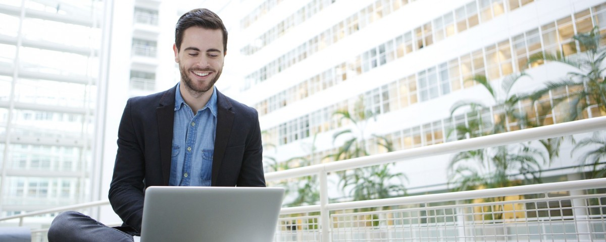 Portrait of a smiling man using laptop computer indoors