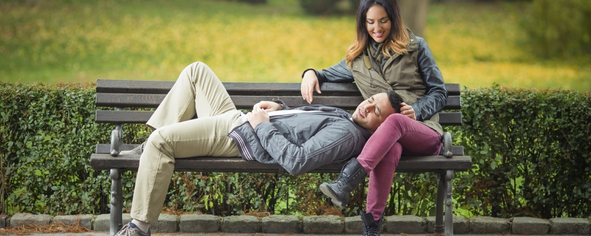Spending your time, Happy young woman sitting on a bench in a park with her boyfriend lying on her lap
